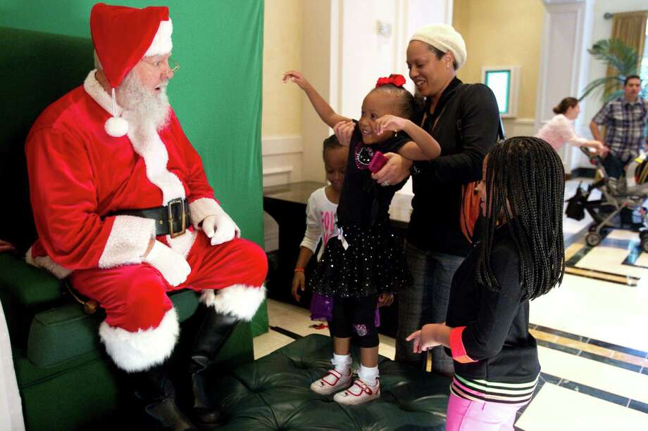 Camari Butler is helped up by her mom, Courtney Butler, to have her picture taken with Santa at Sugar Land Town Square Sunday, Nov. 25, 2012, in Sugar Land. The free photos will be offered on Sundays through December 16. Photo: Brett Coomer, Houston Chronicle / © 2012 Houston Chronicle