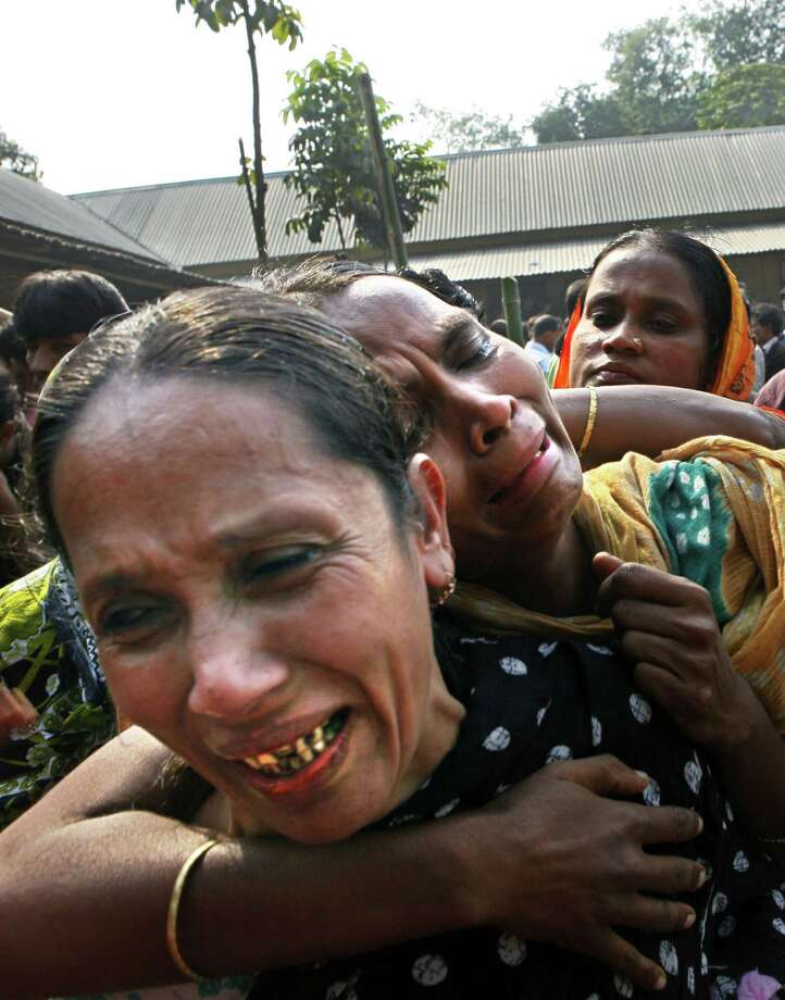 Relatives of garment factory workers killed in a fire cry as they come to collect bodies from a mortuary in Dhaka, Bangladesh, Sunday, Nov. 25, 2012. At least 112 people were killed in a late Saturday night fire that raced through the multi-story garment factory just outside of Bangladesh's capital, an official said Sunday. (AP Photo/Khurshed Rinku) Photo: Khurshed Rinku