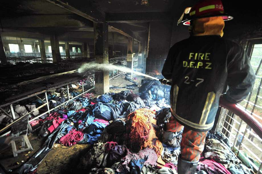 A Bangladeshi firefighter douses the inside of a garment factory outside Dhaka, Bangladesh, Sunday, Nov. 25, 2012. At least 112 people were killed in a late Saturday night fire that raced through the multi-story garment factory just outside of Bangladesh's capital, an official said Sunday. (AP Photo/ khurshed Rinku) Photo: Khurshed Rinku