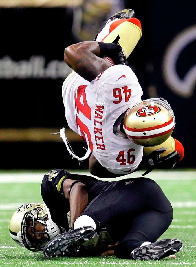 New Orleans Saints free safety Isa Abdul-Quddus, bottom, upends San Francisco 49ers tight end Delanie Walker (46) in the second half of an NFL football game in New Orleans, Sunday, Nov. 25, 2012. Abdul-Quddus was injured on the play. Photo: Bill Haber, Associated Press / FR170136 AP