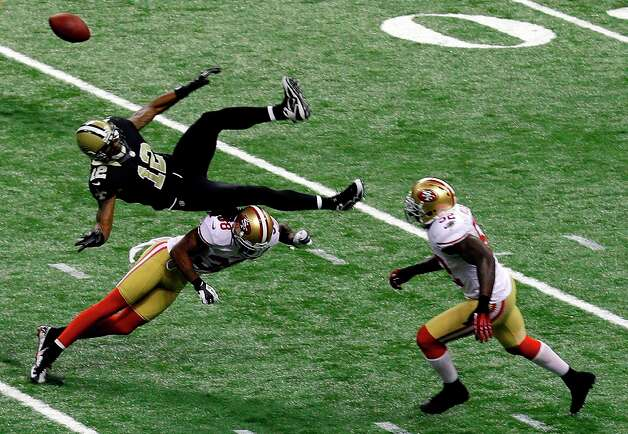 New Orleans Saints wide receiver Marques Colston (12) is upended by San Francisco 49ers strong safety Donte Whitner (31), causing an interception returned for a touchdown, in the second half of an NFL football game in New Orleans, Sunday, Nov. 25, 2012. Photo: Bill Haber, Associated Press / FR170136 AP