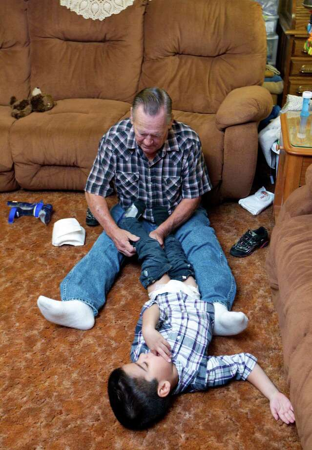 """Geheard Jurek, 67, changes the diaper of his newly adopted son, Anthony, 6, Monday, Nov. 19, 2012, in Angleton.  """"Some people think your not a man if you change diapers, but I don't care,"""" Jurek said.  Having an active retirement, foster parents for more than 34 children over the past nine years, Geheard Jurek , 67, and his wife Judy, 65, adopted special-needs children Christopher, 6, left, and are scheduled to adopt 22-month-old Anthony after Thanksgiving  """"No foster family wanted them but us,"""" Judy said about adopting Christopher and Anthony. """"People tell me we are special, but we feel honored to do this."""" Christopher and Anthony were both born premature with complications. Both children have cerebral palsy, both are legally blind, Christopher is deaf in one ear and Anthony suffers from seizures. Photo: Johnny Hanson, Houston Chronicle / © 2012  Houston Chronicle"""