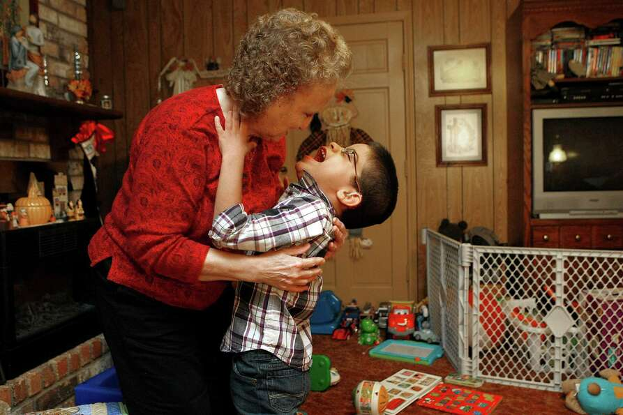 Christopher, 6, laughs with his newly adoptive mother, Judy Jurek, 65, after he walked across the ro