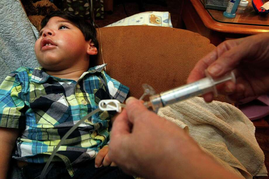 Judy Jurek, 65, flushes the gastrostomy tube after feeding 22-month-old Anthony who can't eat on his own at their home Monday, Nov. 19, 2012, in Angleton.