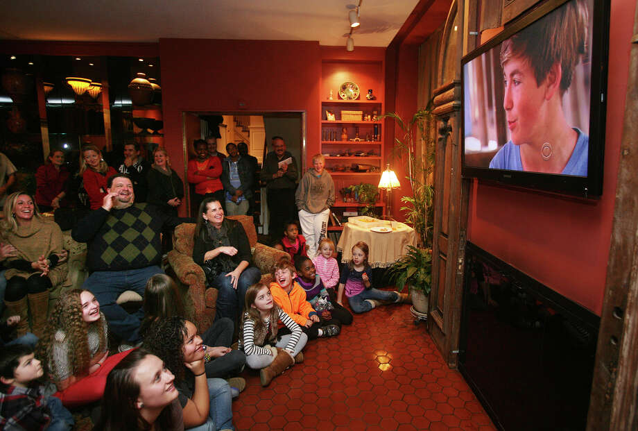 St. Ann School students and their parents watch as St. Ann student Joey Hopkins, 12 of Bridgeport, is interviewed on the television news program 60 Minutes at the home of St. Ann School Principal, Teresa Tillinger, in Bridgeport on Sunday, November 25, 2012. Hopkins and his fellow students appeared on the show because of their work with the charity Free the Children during a recent trip to Kenya. Photo: Brian A. Pounds / Connecticut Post