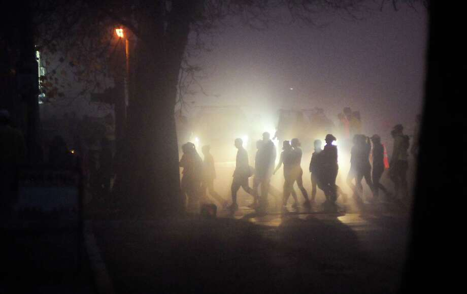 A crowd of people is silhouetted through fog and headlights as they cross Broad St. on their way to the start line of the Seattle Marathon. Photo: Lindsey Wasson  / SEATTLEPI.COM