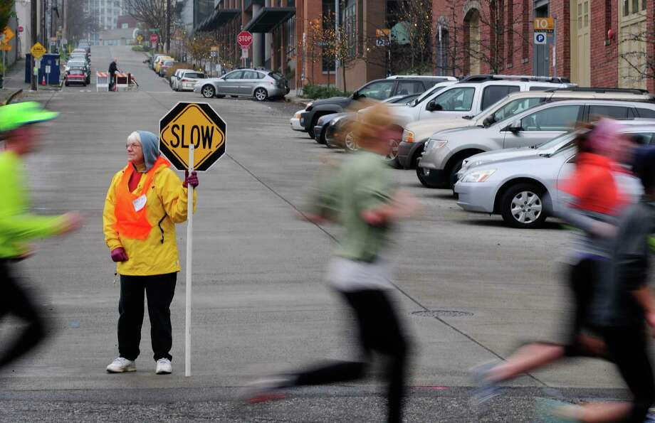 Volunteer Connie Edwards holds a sign that runners took no heed to on Boren Ave. and Republican St. Photo: Lindsey Wasson  / SEATTLEPI.COM