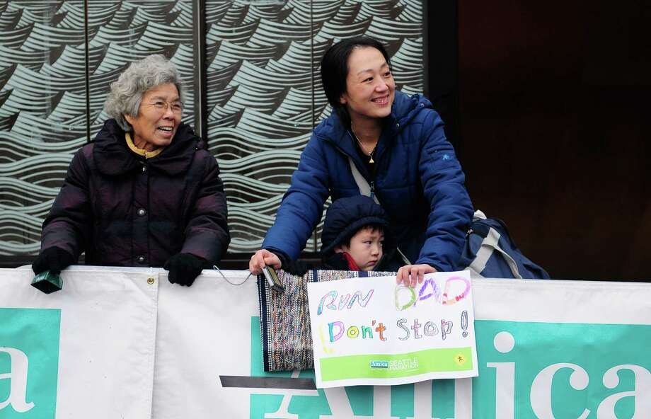 Xiaotun Zhang, right, her son Matthew Wang, 5, and her mother-in-law, Ruiying Liu, left, watch for Zhang's husband, Wenbin Wang, at the start line of  the Seattle Marathon. Photo: Lindsey Wasson  / SEATTLEPI.COM