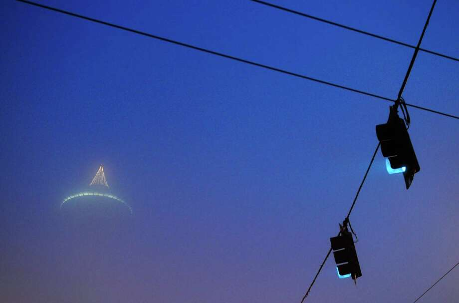 Only the top of the Space Needle can be seen through thick fog at the beginning of the Seattle Marathon. Photo: Lindsey Wasson  / SEATTLEPI.COM