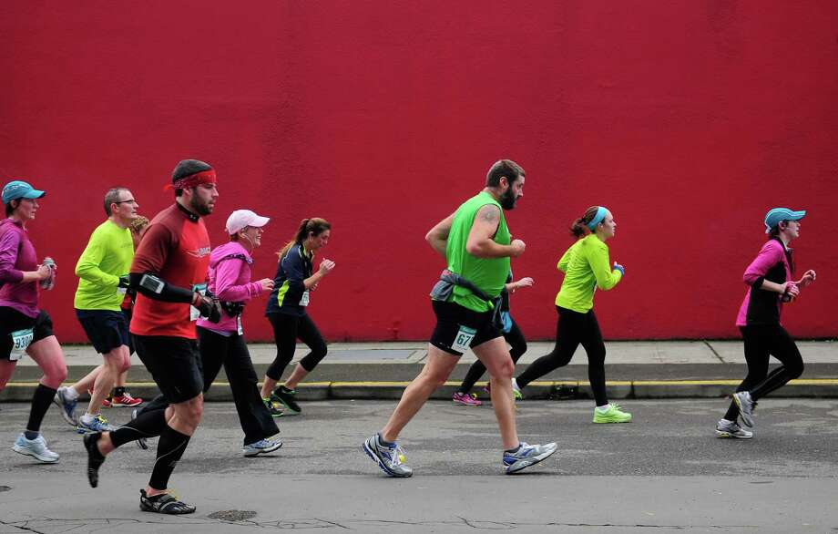 Half marathon runners make their way past the deep red of Glazers Camera. Photo: Lindsey Wasson  / SEATTLEPI.COM
