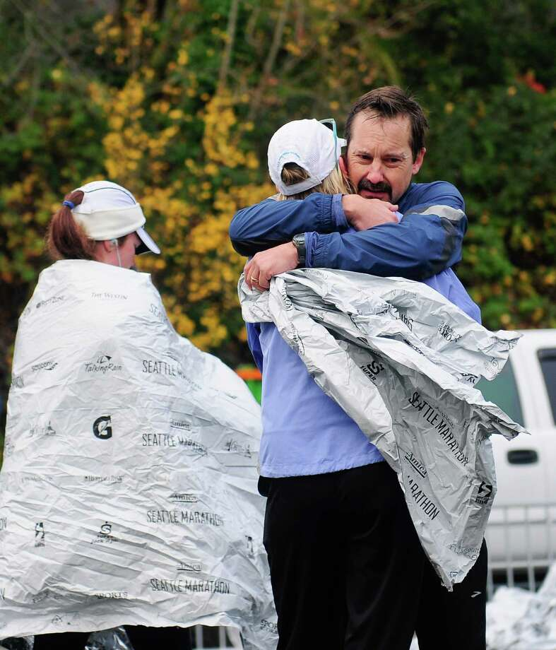 A couple hugs at the end of the course in Memorial Stadium. Photo: Lindsey Wasson  / SEATTLEPI.COM