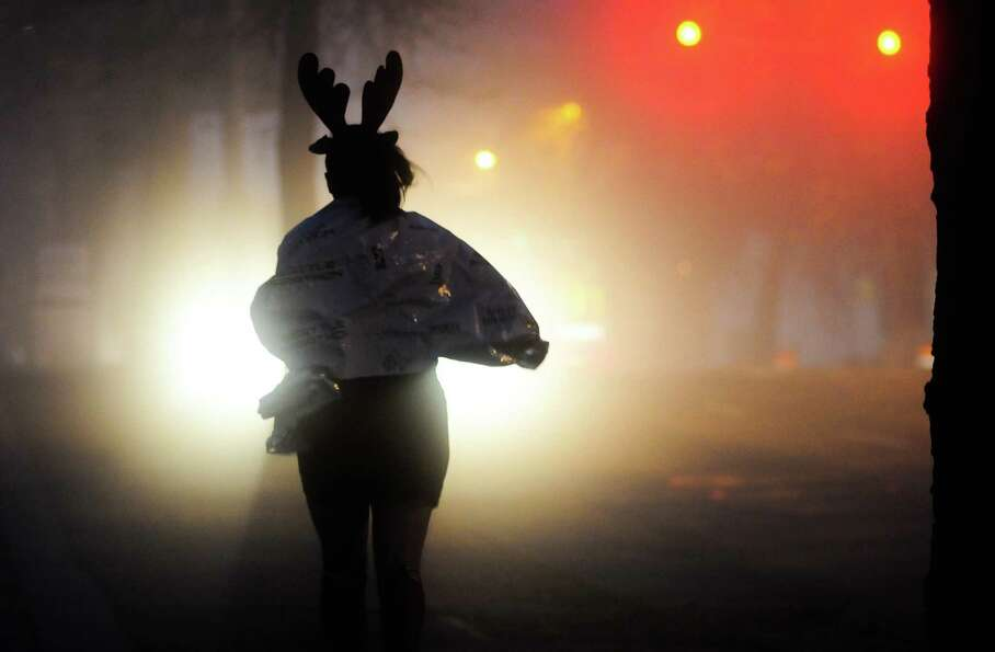 A runner sporting a reindeer headband makes her way to the start line before the Seattle Marathon on