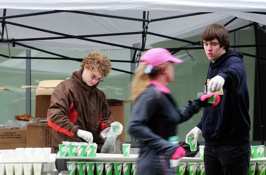 Scott McMains, right, hands out Gatorade to half marathon runners. Photo: Lindsey Wasson  / SEATTLEPI.COM