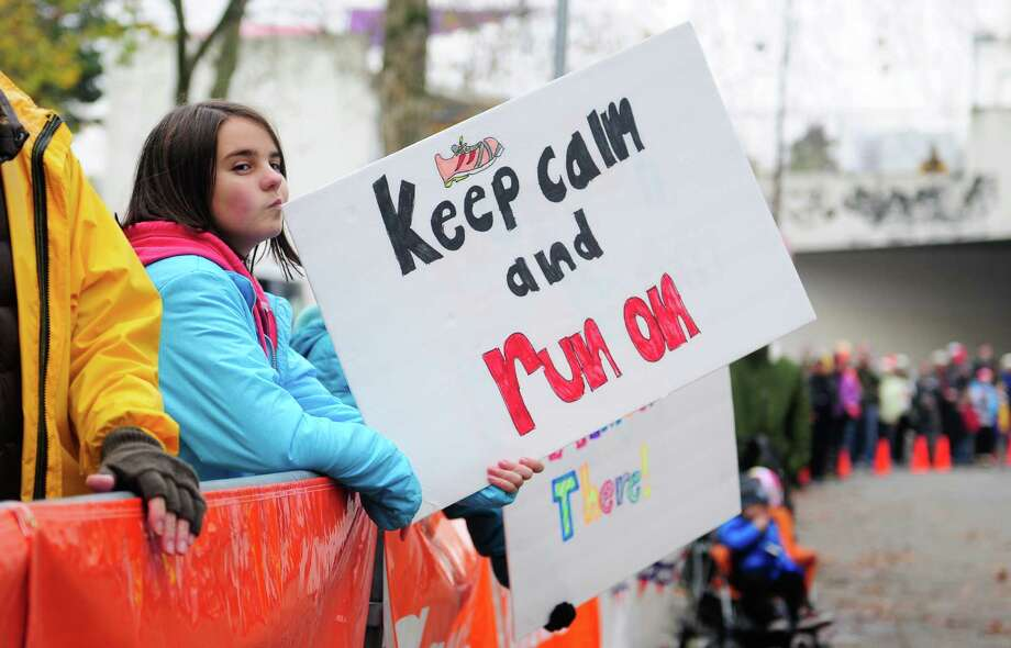 Lucy Beatty, 12, holds an encouraging sign near the entrance of Memorial Stadium. Photo: Lindsey Wasson  / SEATTLEPI.COM