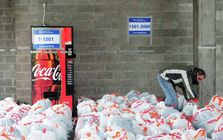 Mike Moore helps prepare the hundreds of clothing bags for pickup in Memorial Stadium. Photo: Lindsey Wasson  / SEATTLEPI.COM