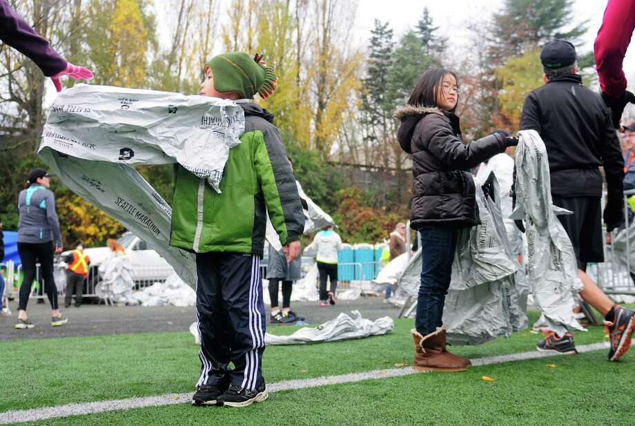Two children hand out space blankets to finishers at Memorial Stadium. Photo: Lindsey Wasson  / SEATTLEPI.COM