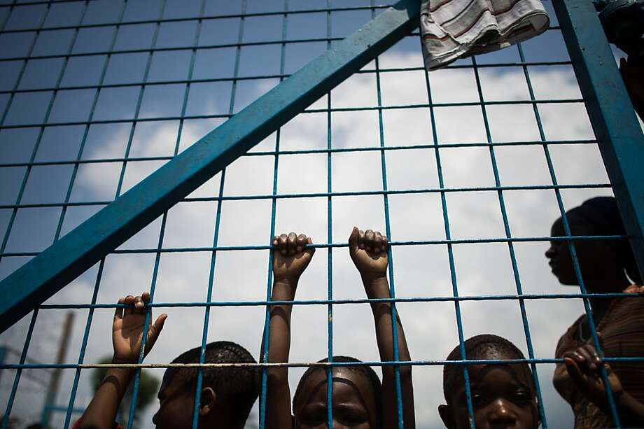 Displaced Congolese children stand against the gate of a religious organisztion on the outskirts of Goma in the east of the Democratic Republic of the Congo on November 25, 2012. Over half a million people have been displaced  in eastern Congo since the outbreak of the M23 rebellion. Diplomatic efforts continued on November 25 to resolve the crisis in eastern DR Congo, with an M23 rebel leader expected to hold further talks with President Joseph Kabila as the African Union called on the rebels to  pull out from Goma. PHIL MOORE/AFP/Getty Images Photo: Phil Moore, AFP/Getty Images