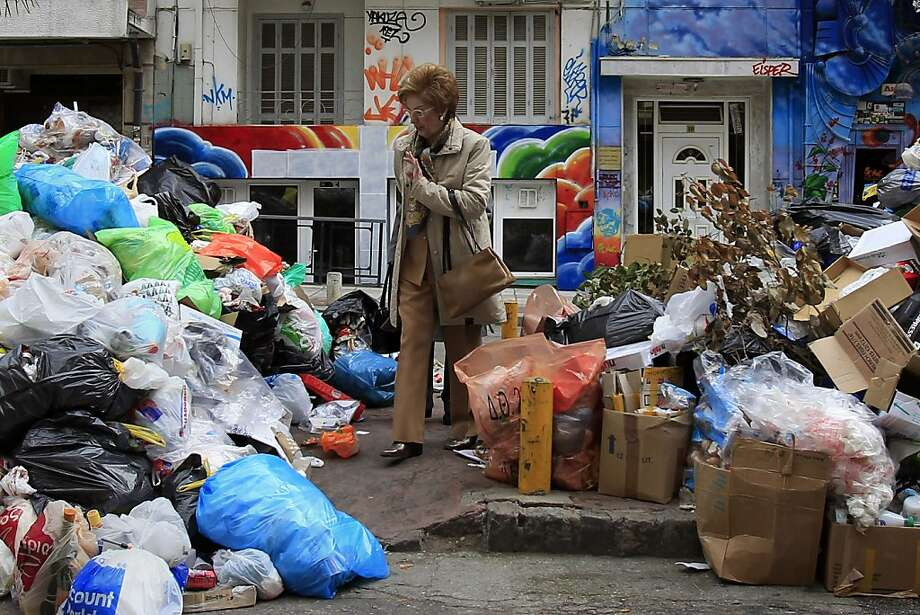 Two women pass among piles of garbage amassed during successive strikes by municipal workers in the northern Greek port city of Thessaloniki, Sunday, Nov. 25, 2012. Government plans to place 2,000 civil servants on notice ahead of reassignment or potential dismissal. (AP Photo/Nikolas Giakoumidis) Photo: Nikolas Giakoumidis, Associated Press