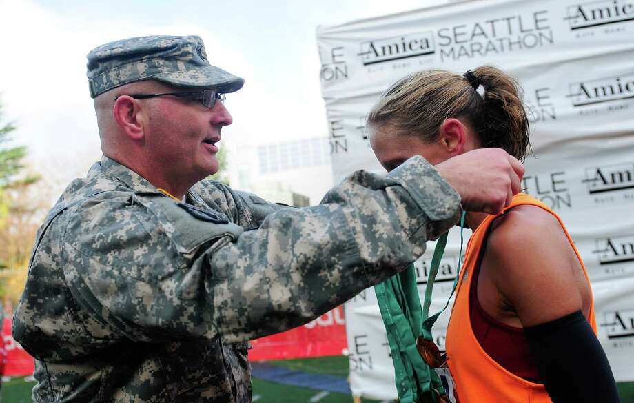 SSgt. Gary Rankins places a medal on Lauren Matthews, the 3rd woman to finish the Seattle Marathon. Photo: Lindsey Wasson  / SEATTLEPI.COM