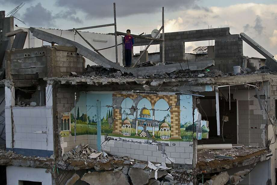 A Palestinian boy looks from the rooftop of a destroyed house in Gaza City, Sunday, Nov. 25, 2012. A leading Islamic cleric in the Gaza Strip has ruled it a sin to violate the recent cease-fire between Israel and the Hamas militant group that governs the Palestinian territory according a religious legitimacy to the truce and giving the Gaza government strong backing to enforce it. (AP Photo/Bernat Armangue) Photo: Bernat Armangue, Associated Press