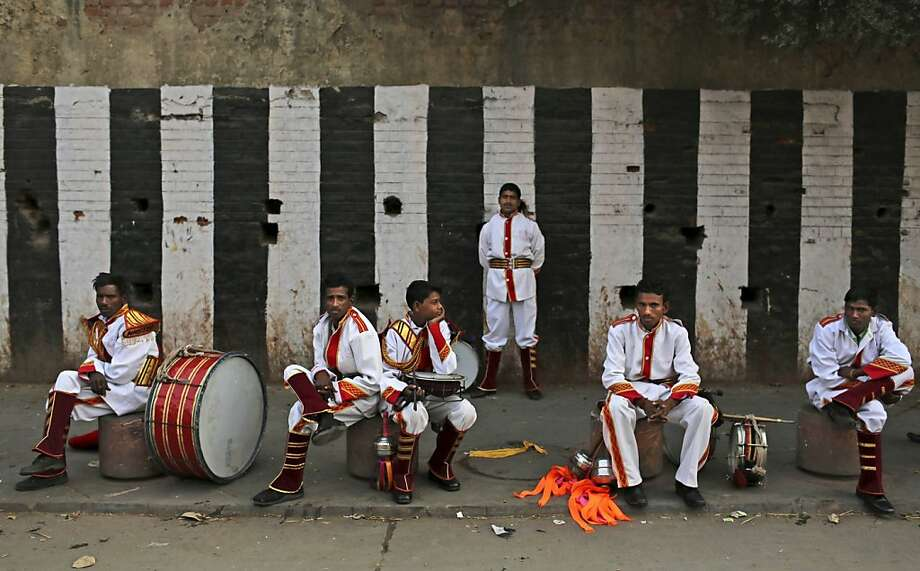 Wedding band:Musicians for an Indian wedding wait for their ride at a bus stop in New Delhi. Photo: Kevin Frayer, Associated Press