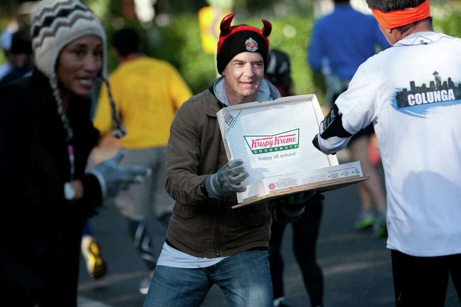 David Peterman tempts runners with doughnuts during the final leg of the Amica Insurance Seattle Marathon. Photo: JOSHUA TRUJILLO / SEATTLEPI.COM