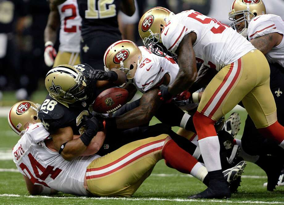 New Orleans Saints running back Mark Ingram (28) loses the ball as he is tackled by San Francisco 49ers defensive end Justin Smith (94) and inside linebacker NaVorro Bowman (53) in the first half of an NFL football game in New Orleans, Sunday, Nov. 25, 2012. (AP Photo/Bill Feig) Photo: Bill Feig
