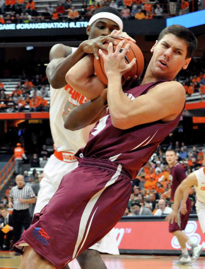 Syracuse's C. J. Fair, left, grapples with Colgate's Luke Roh, right, for the ball during the first half of an NCAA college basketball game in Syracuse, N.Y., Sunday, Nov. 25, 2012. (AP Photo/Kevin Rivoli) Photo: Kevin Rivoli