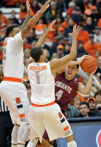 Colgate's Luke Roh (4) is pressured by Syracuse's Dajuan Coleman, left, and Michael Carter-Williams during the first half of an NCAA college basketball game in Syracuse, N.Y., Sunday, Nov. 25, 2012. (AP Photo/Kevin Rivoli) Photo: Kevin Rivoli