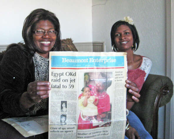 Wanda Petry holds up a laminated front page from The Beaumont Enterprise dated Nov. 26, 1985 with a photo of her and her daughter Ashleigh, who was one of two cojoined twins born to her the year before. Ashleigh's sister, Alma, never fully recovered from the surgery that separated them the day after they were born. Ashleigh, right, has lead an otherwise normal life after her much heralded birth and infancy. Photo: Sarah Moore