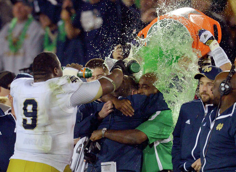 Notre Dame coach Brian Kelly, center left, is doused as he hugs an unidentified team member after Notre Dame defeated Southern California 22-13 in an NCAA college football game, Saturday, Nov. 24, 2012, in Los Angeles. (AP Photo/Mark J. Terrill) Photo: Mark J. Terrill