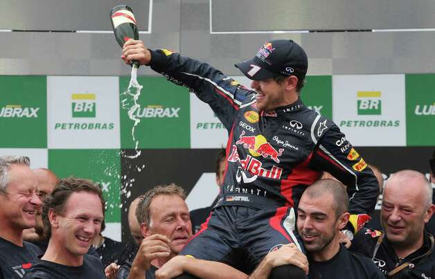 Red Bull driver Sebastian Vettel of Germany, top, sprays champagne on his teammates after the Brazil's Formula One Grand Prix at the Interlagos race track in Sao Paulo, Brazil,  Sunday, Nov. 25, 2012. Vettel overcame a first-lap crash to clinch his third straight Formula One championship title on Sunday, finishing sixth in an incident-filled Brazilian Grand Prix won by Jenson Button under pouring rain.(AP Photo/Andre Penner) Photo: Andre Penner