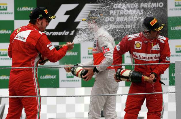 Ferrari driver Fernando Alonso. left, of Spain, sprays champagne on teammate Felipe Massa, of Brazil at the podium of the Formula One Brazilian Grand Prix at Interlagos race track in Sao Paulo, Brazil, Sunday, Nov. 25, 2012. Red Bull driver Sebastian Vettel, of Germany, overcame a first-lap crash to clinch his third straight Formula One championship title on Sunday, finishing sixth in an incident-filled Brazilian Grand Prix won by Jenson Button under pouring rain. (AP Photo/Victor R. Caivano) Photo: Victor R. Caivano