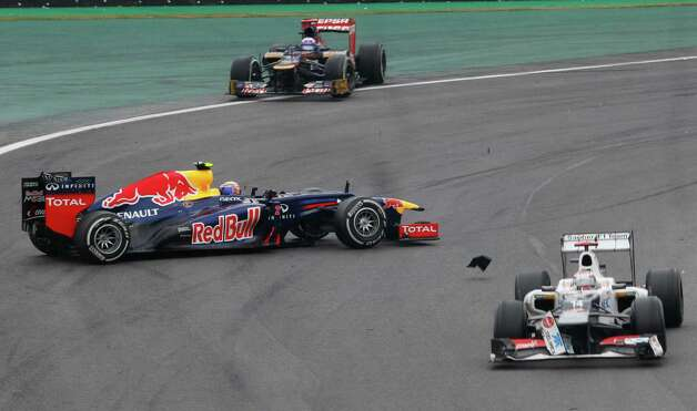 Red Bull driver Mark Webber, left, of Australia, looses control of his car after colliding with Sauber driver Sergio Perez of Mexico, right, during the Formula One Brazilian Grand Prix at the Interlagos race track in Sao Paulo, Brazil, Sunday, Nov. 25, 2012. (AP Photo/Silvia Izquierdo) Photo: Silvia Izquierdo
