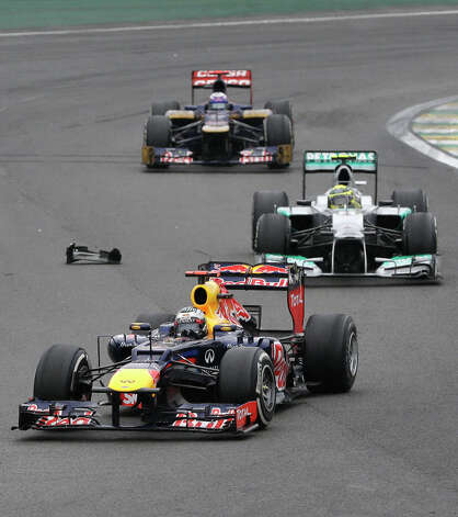 Red Bull driver Sebastian Vettel of Germany, front, steers his car ahead of Mercedes Grand Prix driver Nico Rosberg of Germany. center, and Toro Rosso driver Daniel Ricciardo of Australia as they drive by a car debris from Mark Wabber's car during the Formula One Brazilian Grand Prix at the Interlagos race track in Sao Paulo, Brazil, Sunday, Nov. 25, 2012. (AP Photo/Ricardo Mazalan) Photo: Ricardo Mazalan
