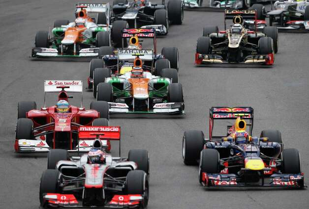 Red Bull driver Mark Webber of Australia, right, McLaren Mercedes driver Jenson Button of Britain, front second from  left, and Ferrari driver Fernando Alonso of Spain (5), at left,  steer their cars during the Formula One Brazilian Grand Prix at the Interlagos race track in Sao Paulo, Brazil, Sunday, Nov. 25, 2012. (AP Photo/Silvia Izquierdo) Photo: Silvia Izquierdo