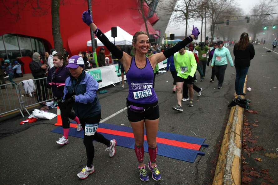 A runner strikes a pose at the start during the Amica Insurance Seattle Marathon on Sunday, November