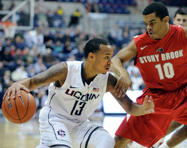 Connecticut's Shabazz Napier, left, drives past Stony Brook's Carson Puriefoy during the first half of Connecticut's 73-62 victory in an NCAA college basketball game, Sunday, Nov. 25, 2012, in Storrs, Conn. Nappier scored a game-high 19 in the victory. (AP Photo/Fred Beckham) Photo: Fred Beckham, Associated Press / FR153656 AP
