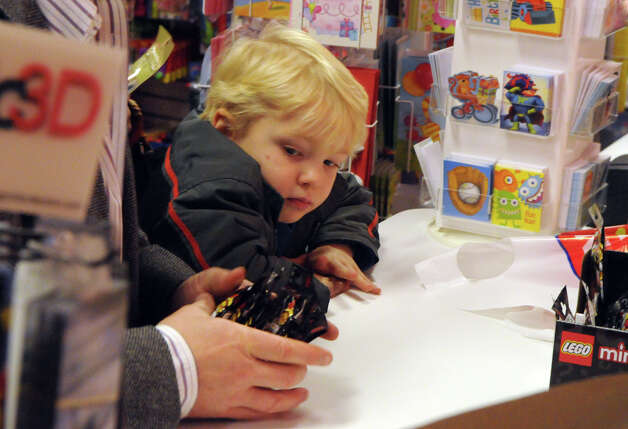 Leo Ford, 6, keeps an eye on his father's purchases at Smart Kids' Toys on East Elm Street in Greenwich, Conn., Nov. 25, 2012. Photo: Keelin Daly / Stamford Advocate Riverbend Stamford, CT