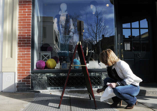 Liz Logie, owner of Atelier 360, writes sale information on a sign outside her new Greenwich Avenue shop in Greenwich, Conn., Nov. 25, 2012. Photo: Keelin Daly / Stamford Advocate Riverbend Stamford, CT