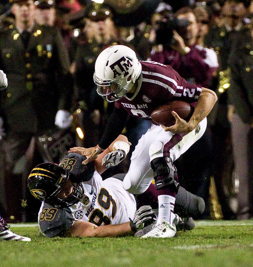 Johnny Manziel gets away from Missouri's Matt Hoch before throwing a touchdown pass Saturday night. Photo: Nick De La Torre, Staff / © 2012  Houston Chronicle