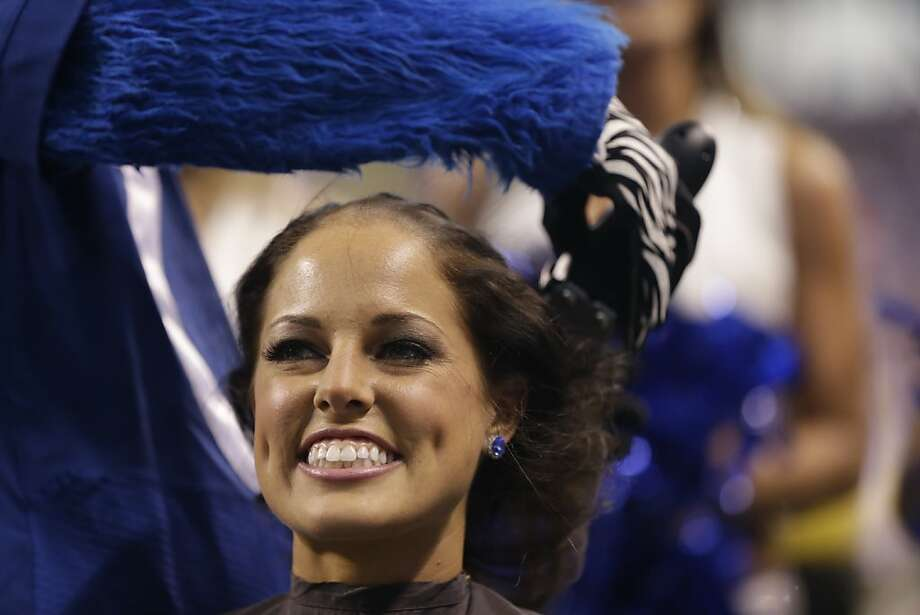 Indianapolis Colts cheerleader Megan M.has her head shaved by the Blue the Colts mascot during the second half of an NFL football game between the Indianapolis Colts and the Buffalo Bills in Indianapolis, Sunday, Nov. 25, 2012. Money was raised for leukemia research in honor of head coach Chuck Pagano.  (AP Photo/Darron Cummings) Photo: Darron Cummings, Associated Press