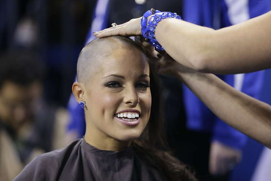 Indianapolis Colts cheerleader Megan M. has her head shaved by the Blue the Colts mascot during the second half of an NFL football game between the Indianapolis Colts and the Buffalo Bills in Indianapolis, Sunday, Nov. 25, 2012. Money was raised for leukemia research in honor of head coach Chuck Pagano.  (AP Photo/Darron Cummings) Photo: Darron Cummings, Associated Press