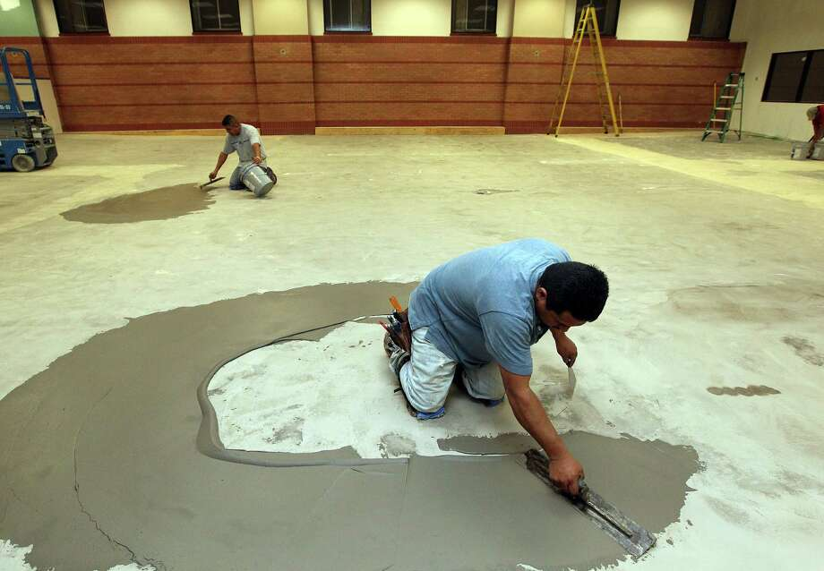 Francisco Herrera, right, and Ruben Chavez, left, prepared the floor to install carpet in the new Harris County law library on the first floor of Congress Plaza at 1019 Congress Tuesday, Nov. 20, 2012, in Houston.  The Harris County law library is intended to be more useful and accessible to the public, and with free legal advice on offer, is nearing completion. The estimated $600,000 build-out, overseen by County Attorney Vince Ryan, whose department runs the library is using the space where jurors assembled prior to a new jury building opening last year. Photo: Johnny Hanson, Staff / © 2012  Houston Chronicle