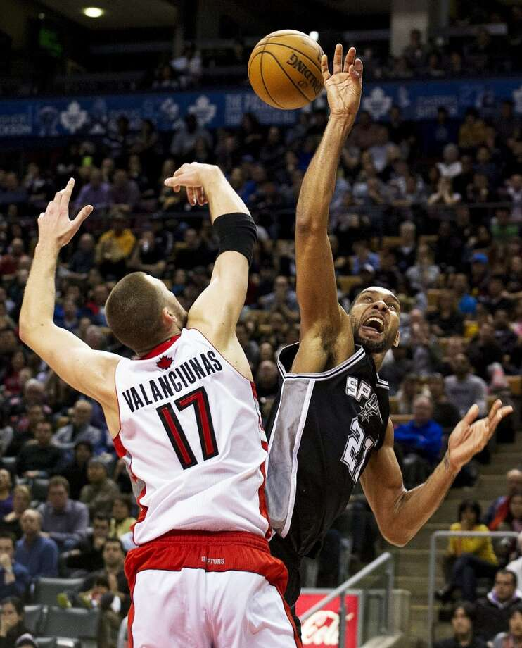 San Antonio Spurs' Tim Duncan (21) is fouled while going to the basket by Toronto Raptors' Jonas Valanciunas during the second half of an NBA basketball game, Sunday, Nov. 25, 2012, in Toronto. The Spurs won 111-106. (AP Photo/The Canadian Press, Aaron Vincent Elkaim) (Associated Press)