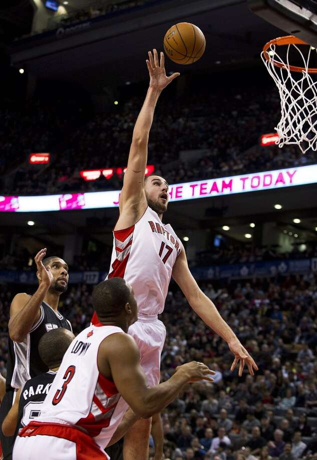 Toronto Raptors' Jonas Valanciunas (17) shoots past San Antonio Spurs' Tim Duncan, left, during the first half of an NBA basketball game, Sunday, Nov. 25, 2012, in Toronto. (AP Photo/The Canadian Press, Aaron Vincent Elkaim) (Associated Press)
