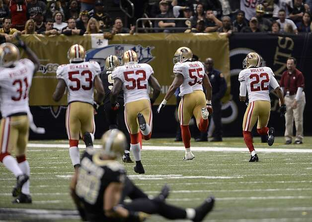 Ahmad Brooks (55) leads a gaggle of 49ers as he returns an interception for a game-changing touchdown just before halftime. Photo: Bill Feig, Associated Press