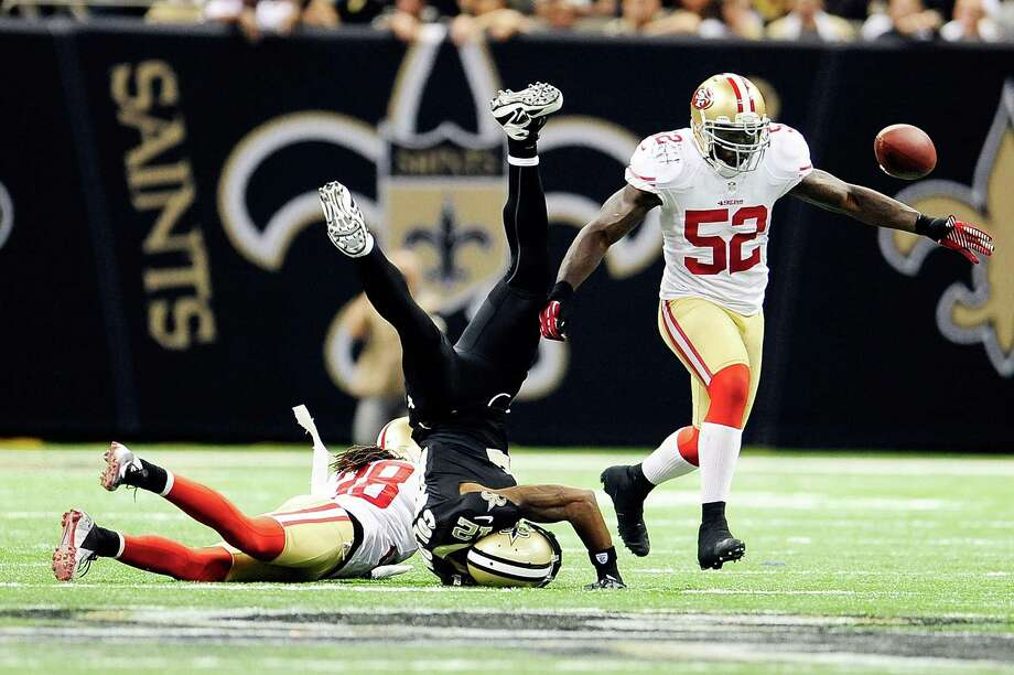Saints receiver Marques Colston is upended by the 49ers' Dashon Goldson (38) as Patrick Willis (52) makes a play for the deflected ball, which was snagged by Donte Whitner and returned 42 yards for a touchdown in the third quarter. Photo: Stacy Revere, Stringer / 2012 Getty Images
