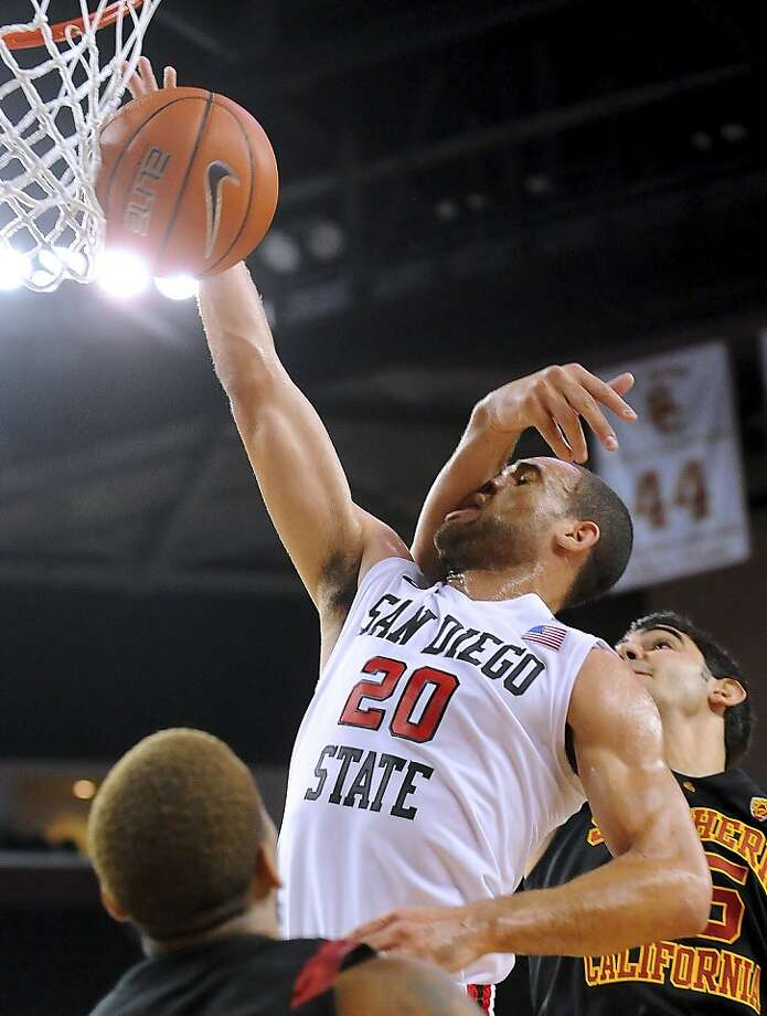 San Diego State forward JJ O'Brien (20) drives to the basket as he tangles with Southern California center Omar Oraby, rear right, during the first half of an NCAA college basketball game, Sunday, Nov. 25, 2012, in Los Angeles. (AP Photo/Gus Ruelas) Photo: Gus Ruelas, Associated Press