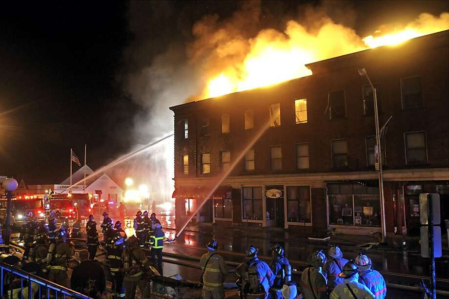 Firefighters from Leominster and surrounding cities and towns battle a six-alarm fire in at the old Columbia Hotel building on Main Street of Leominster, Mass., early Sunday morning, Nov. 25, 2012.   (AP Photo/Steve Lanava, Telegram & Gazette)) Photo: (STEVE LANAVA/T&G Staff Photo), Associated Press